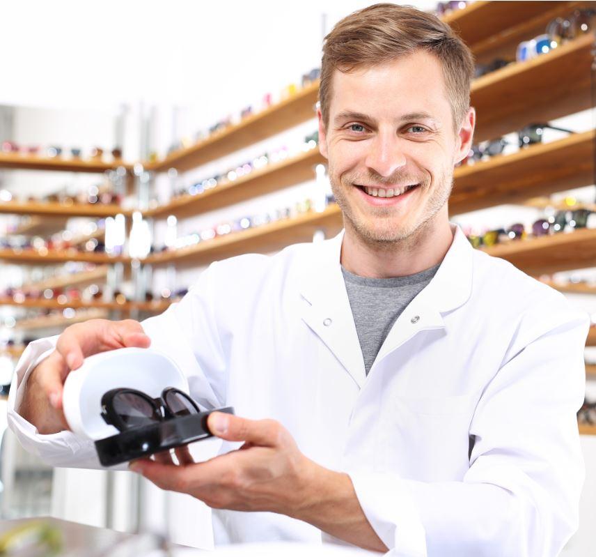 oculista optometrista con in mano paio di occhiali lenti fotocromatiche
