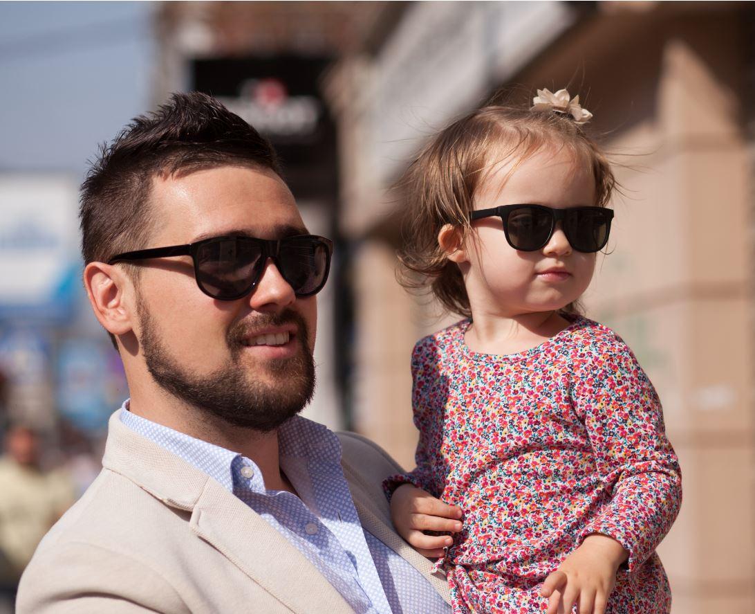 papà con bambina in braccio entrambi indossano occhiali da sole