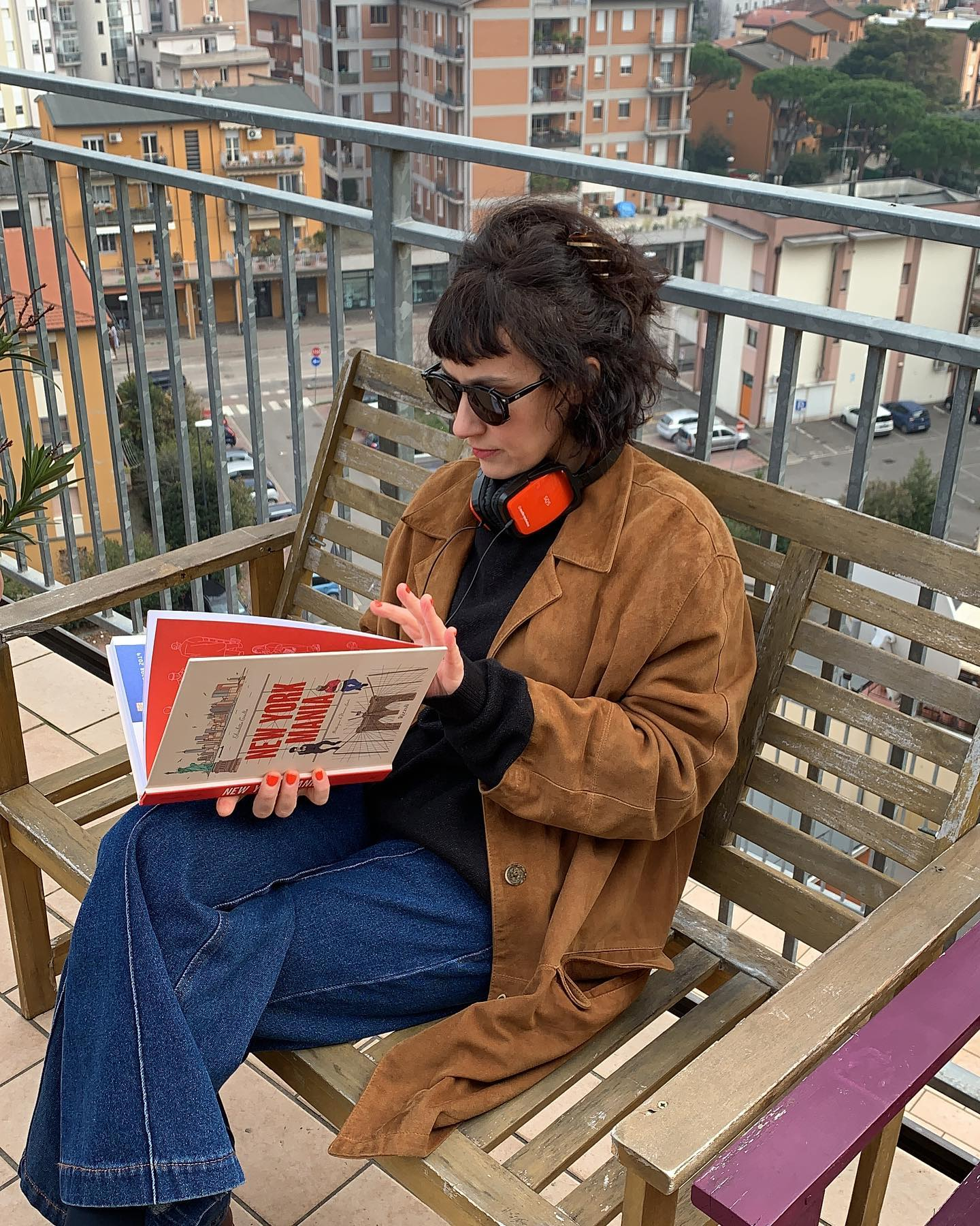 ragazza seduta su panchina con in mano libro su New York e indosso occhiali da sole Moscot