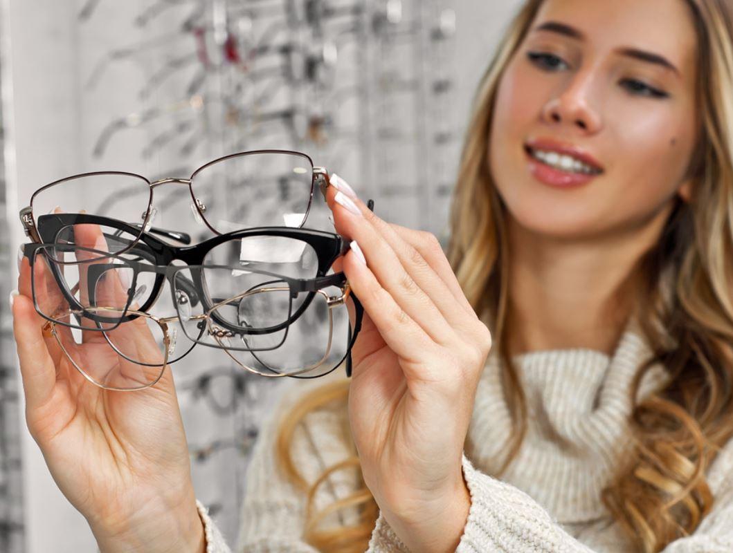 ragazza con tanti occhiali da vista in mano
