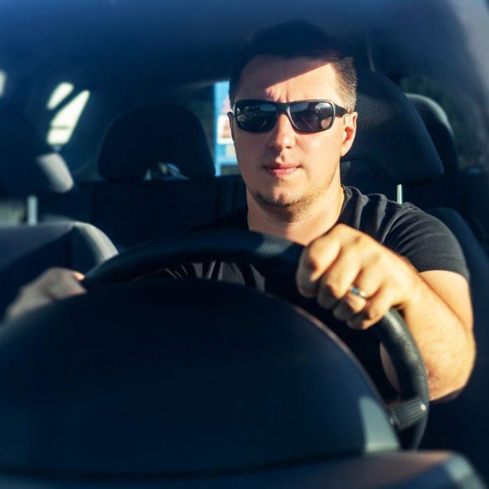 ragazzo alla guida con occhiali da sole