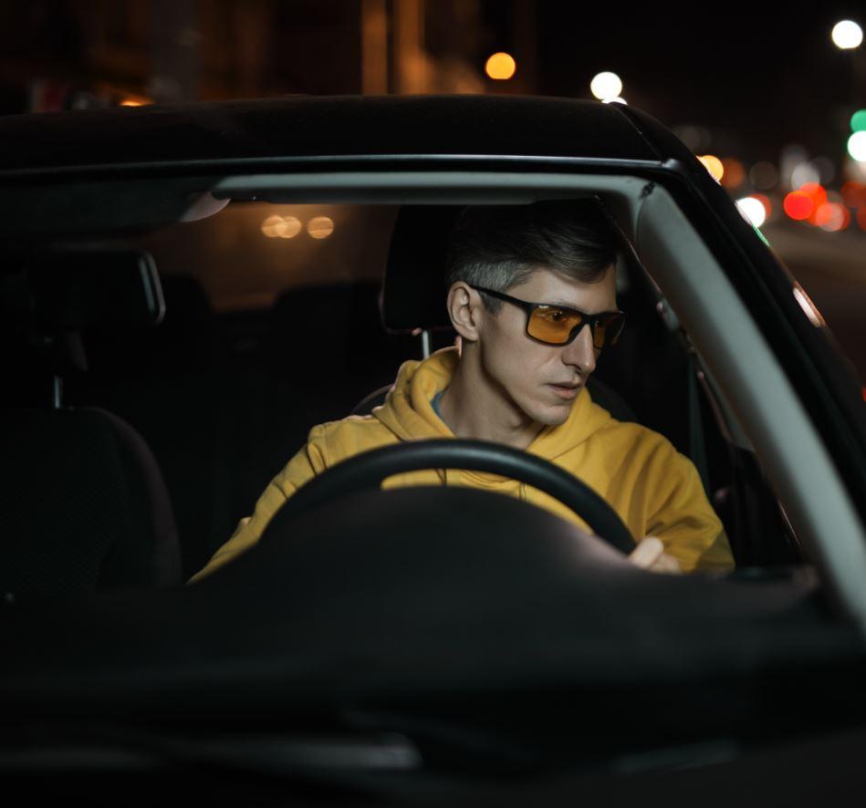 ragazzo alla guida con occhiali lenti colorate