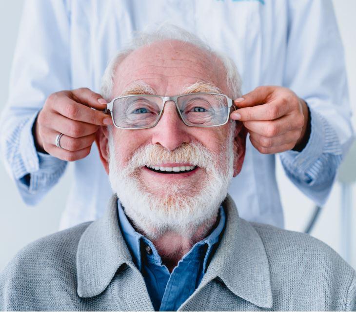 ottico aiuta uomo adulto a indossare occhiali da vista