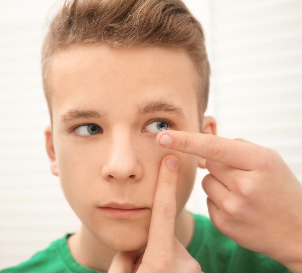 ragazzino intento a mettersi lenti a contatto
